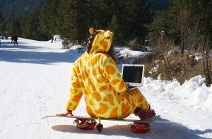 איש מחופש לג'רפה עם מחשב נייד על הברכיים גולש בבנסקו